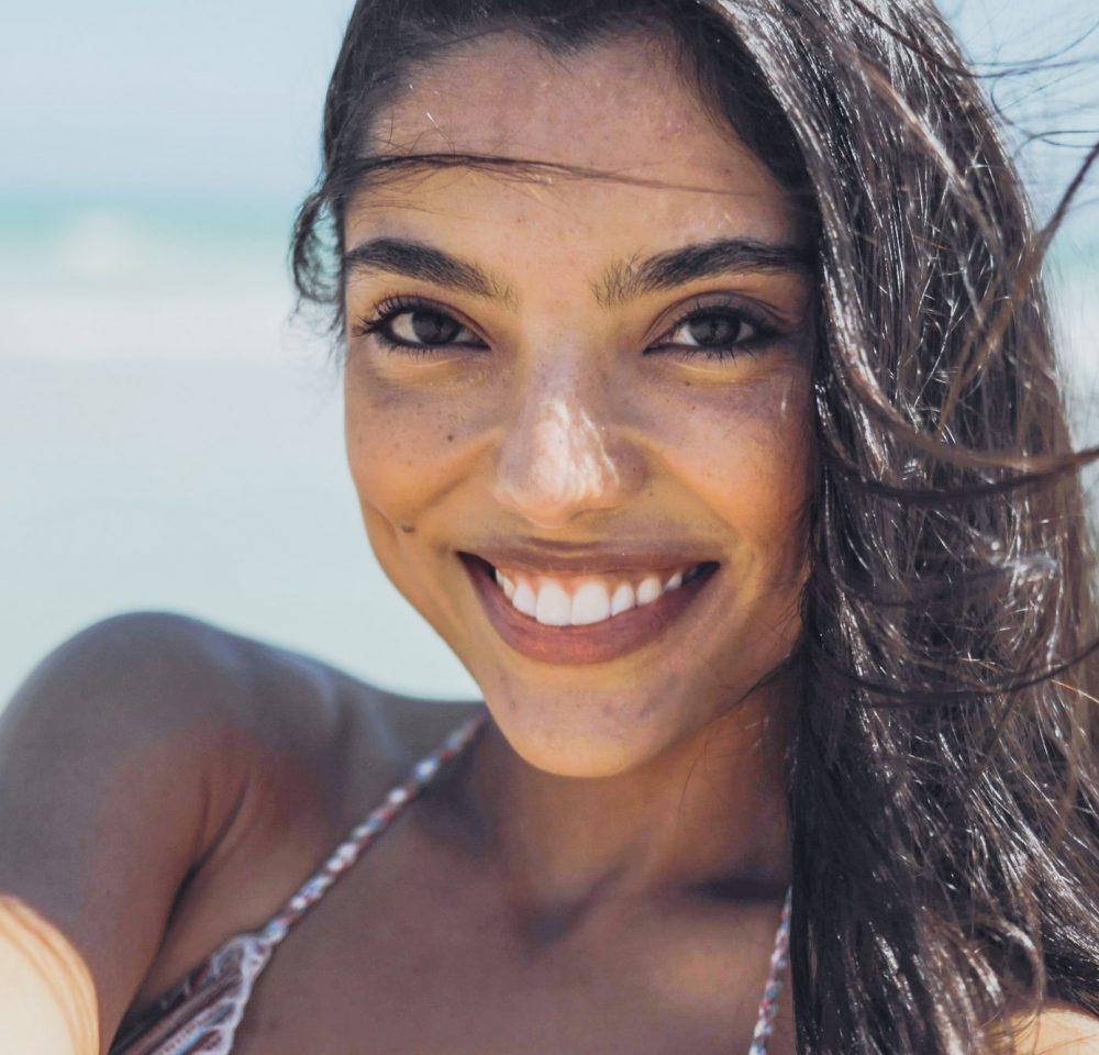 Charming ethnic woman on windy beach